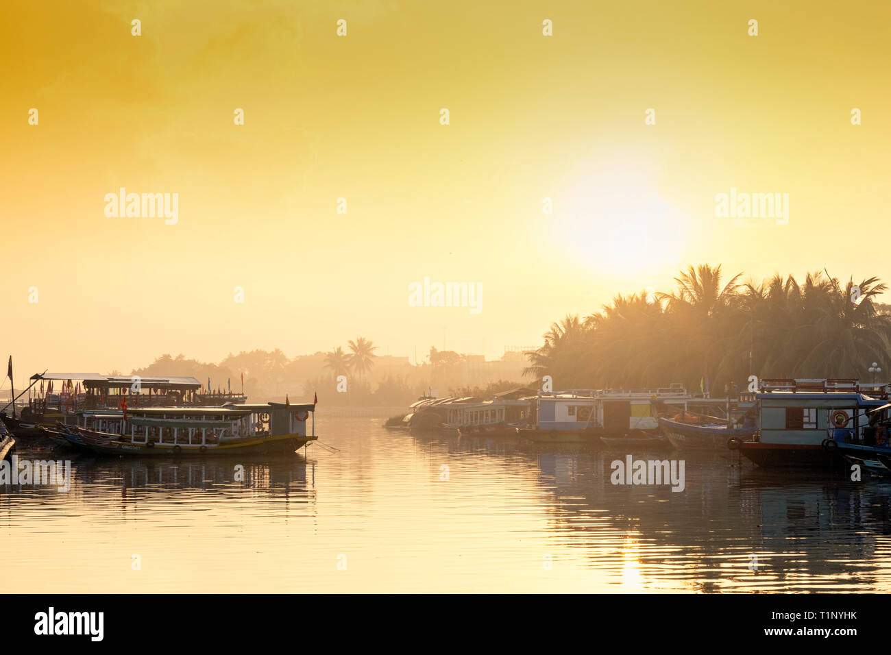Golden light on the Thu Bon river in Hot An, showing silhouetted boats - Stock Image