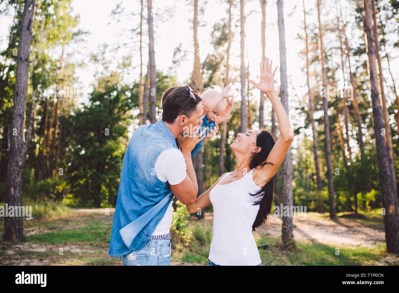 Family mom, dad and daughter sits at the daddy on the shoulders, and parents kiss on the nature in the forest in the summer at sunset - Stock Image