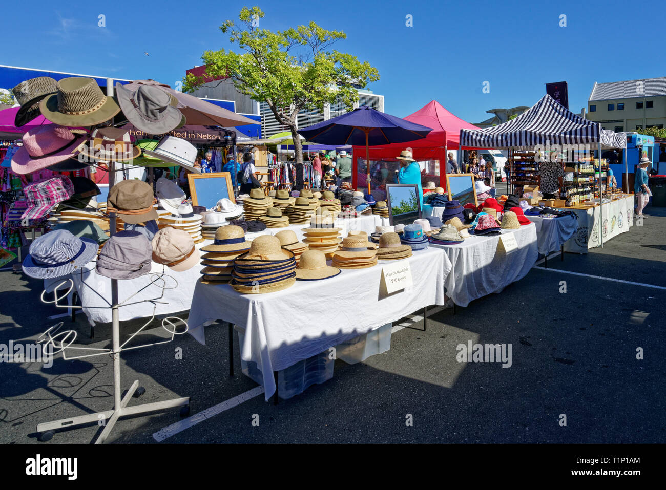 Stacks of straw hats on a Nelson market stall on a sunny day. Nelson, New Zealand. - Stock Image