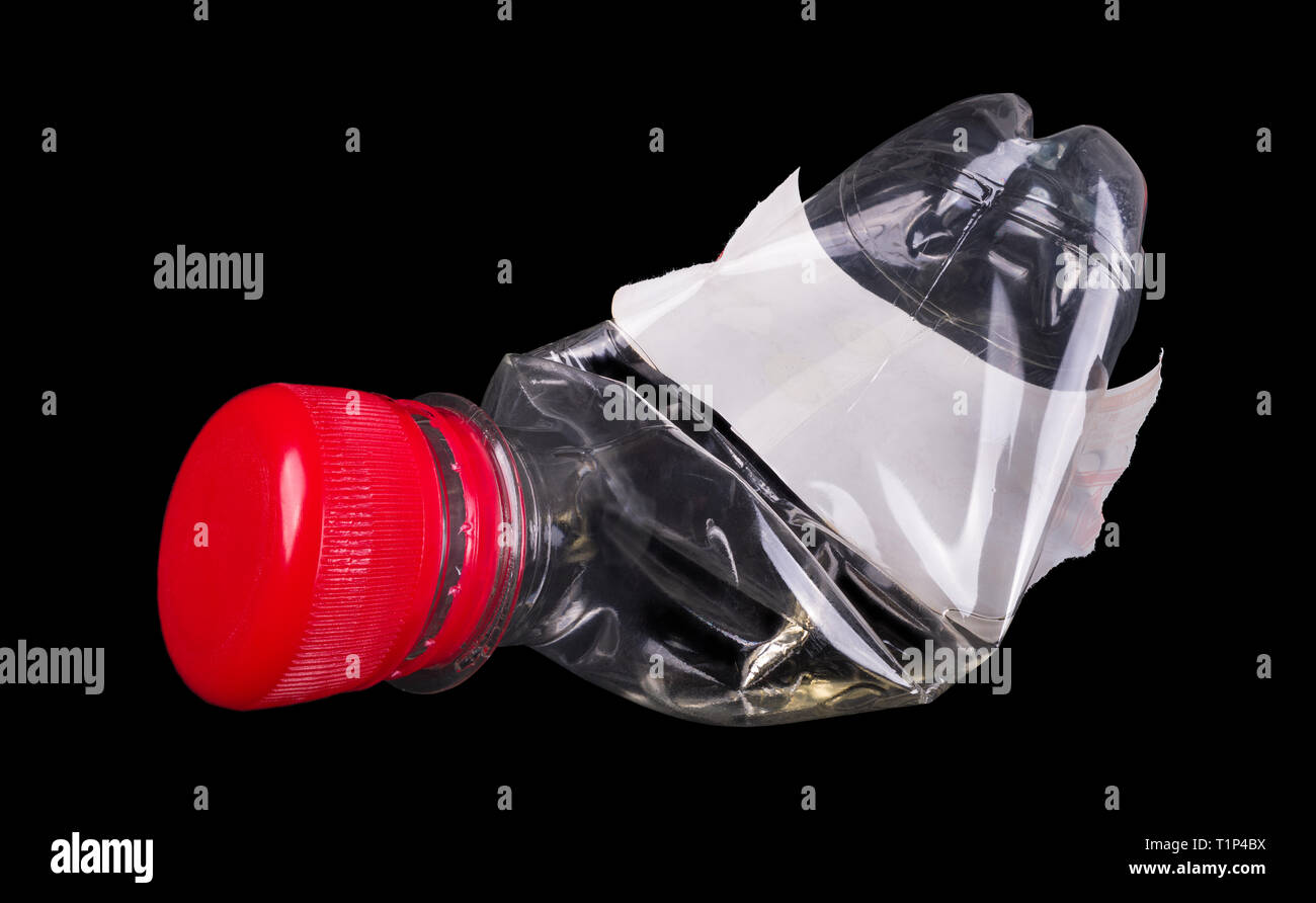 Used plastic bottle. Red cap. White label. Isolated. Black background. One empty transparent PET beverage wrapping. Waste sorting, recycling, disposal. - Stock Image