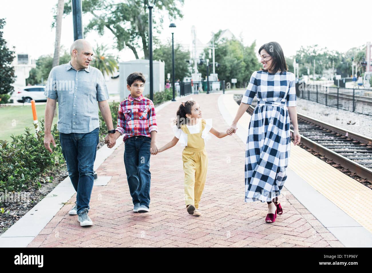 Family holding hand walking next train rail track - Stock Image