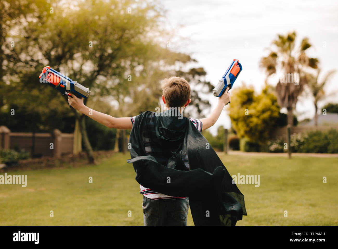 Rear view of boy wearing a black cape and running with two toy guns in hand. Young boy playing dressed up in cape. - Stock Image