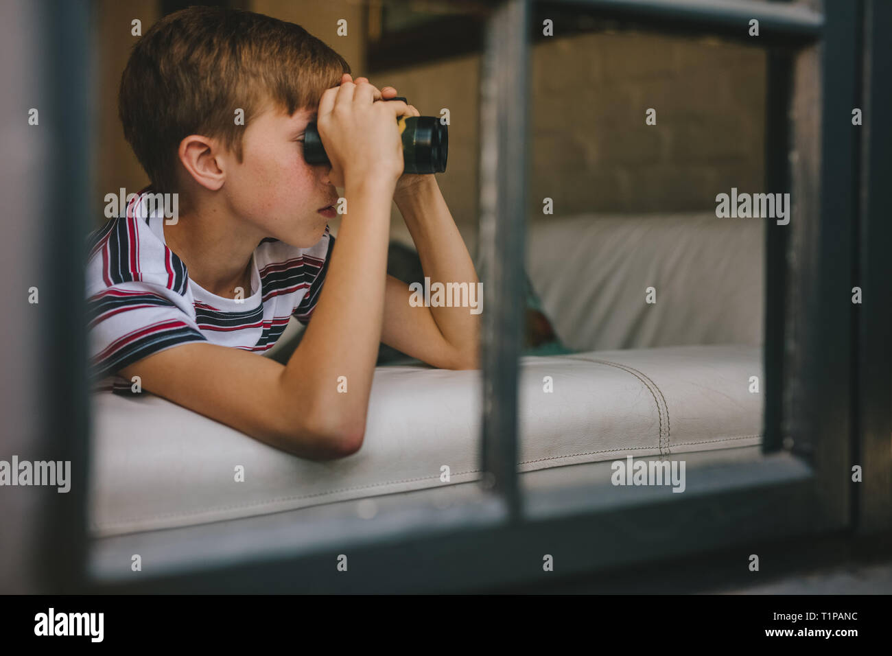 Curious boy looking out the window with binocular. Small boy on sofa looking outside window using binoculars. - Stock Image