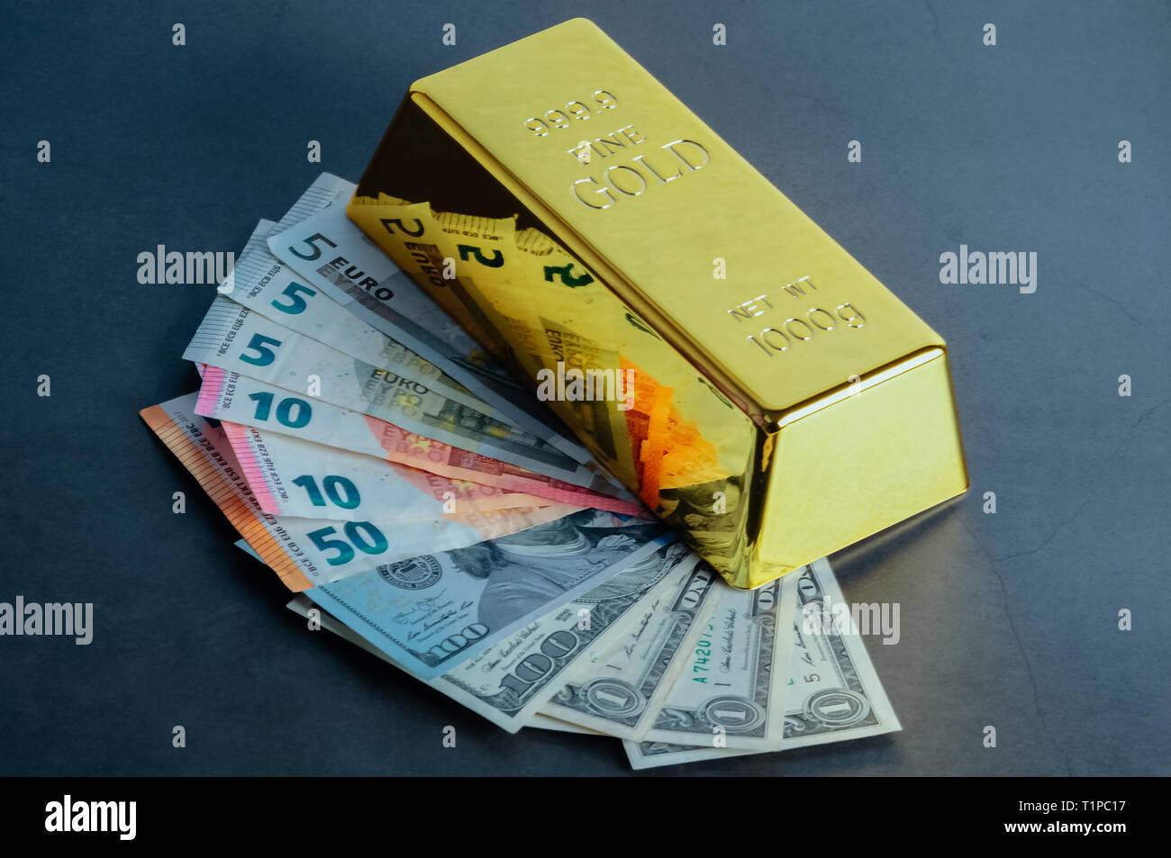 Gold bar ingot bullion against the background of dollar and euro bills - Stock Image