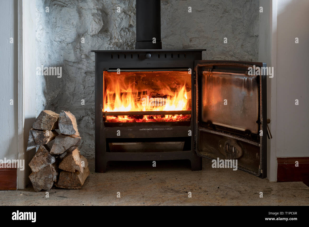 Wood burning in a woodburning stove with a pile of logs. Scotland - Stock Image