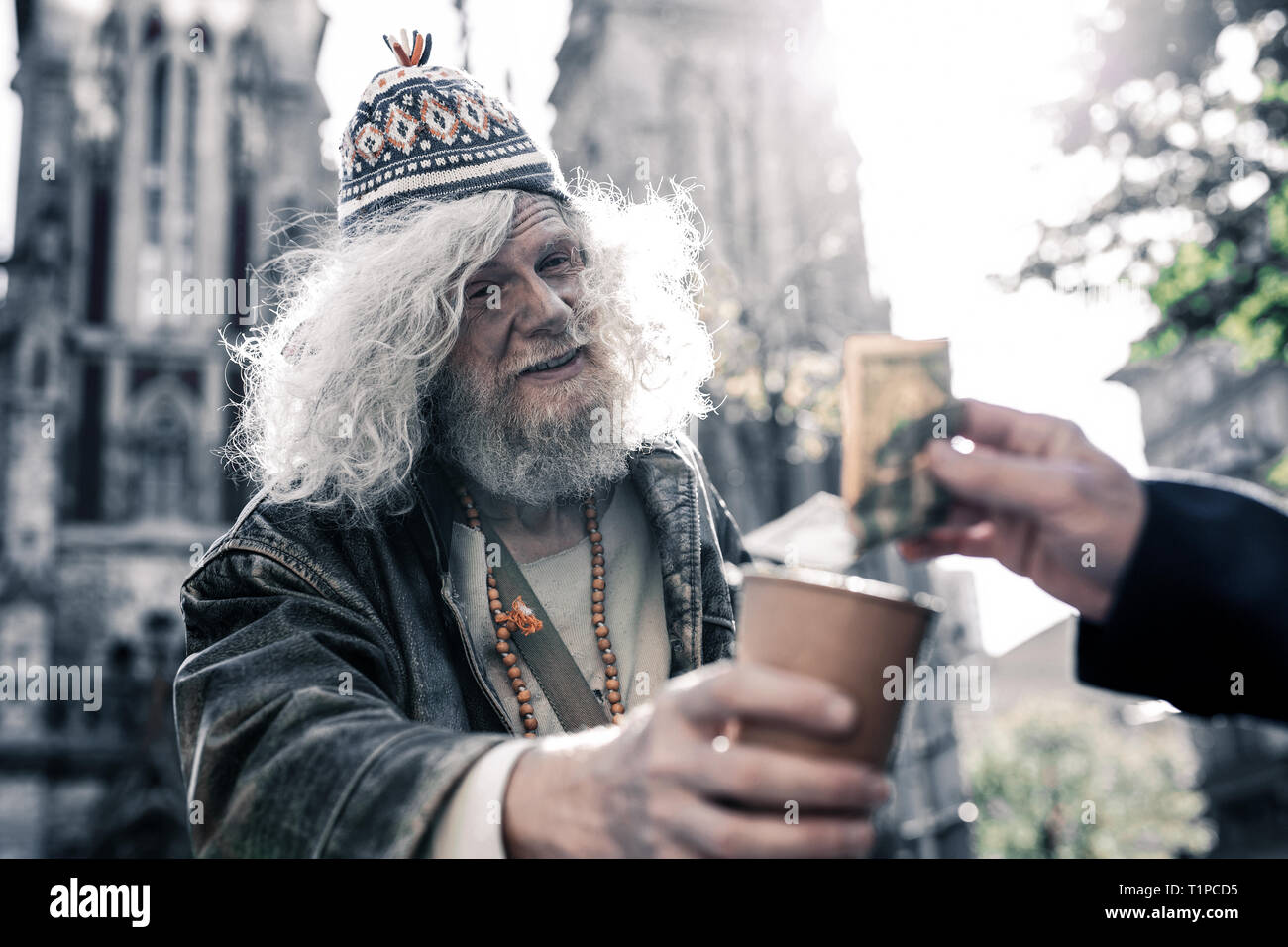 Dirty long-haired homeless wearing funky clothes and asking for money - Stock Image
