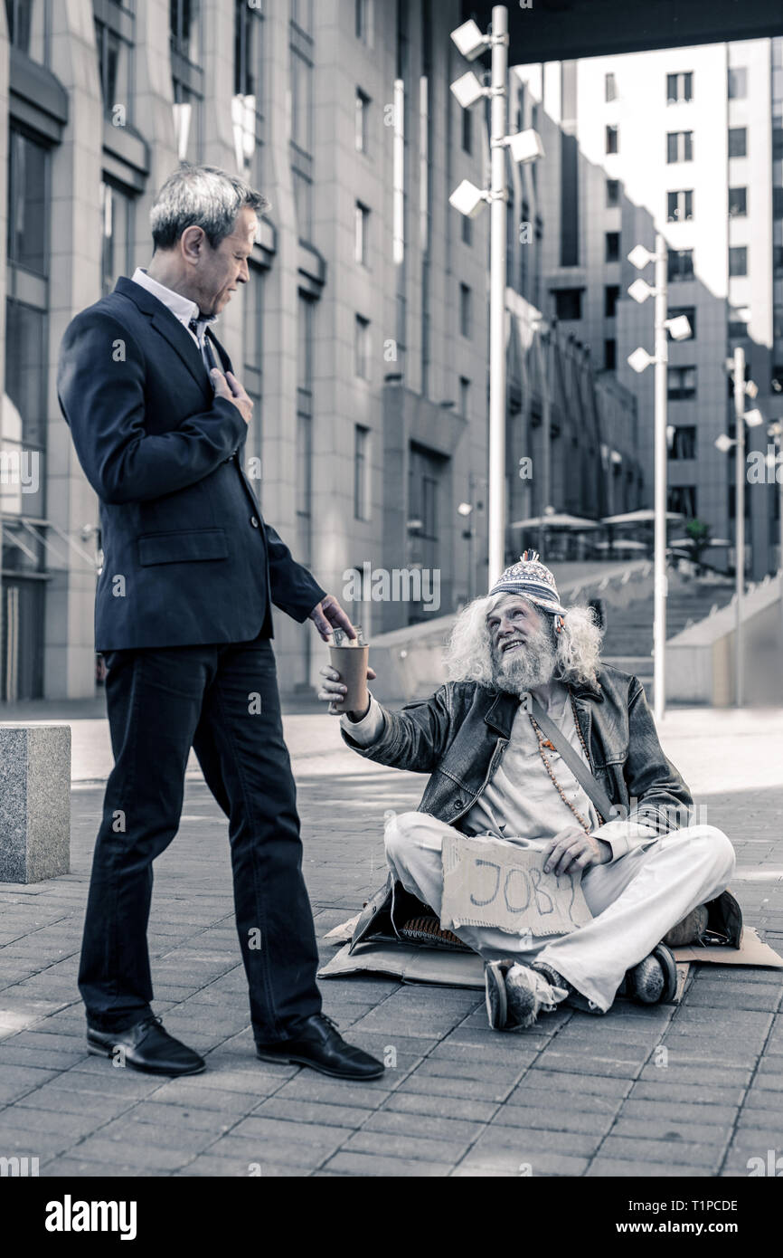 Old grey-haired man being jobless and living on street - Stock Image