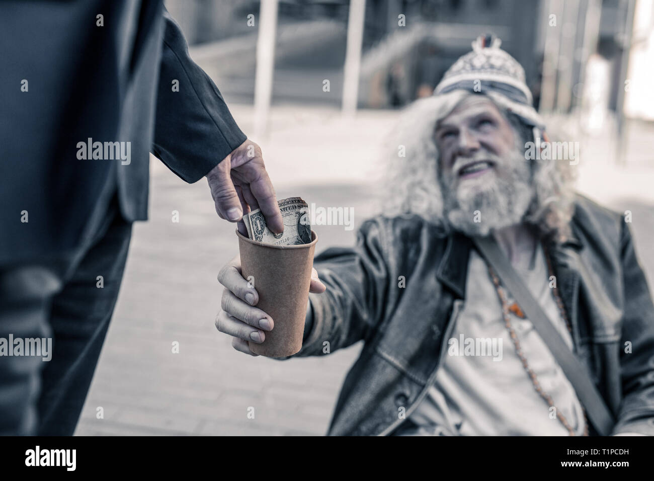 Thankful homeless man with dirty hair stretching empty coffee cup - Stock Image