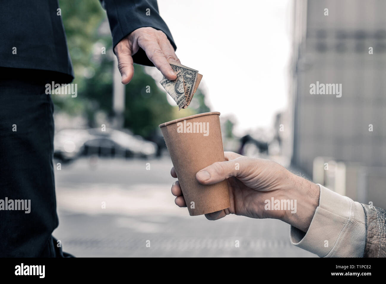 Rich business man stopping on street and compassionately sharing money - Stock Image