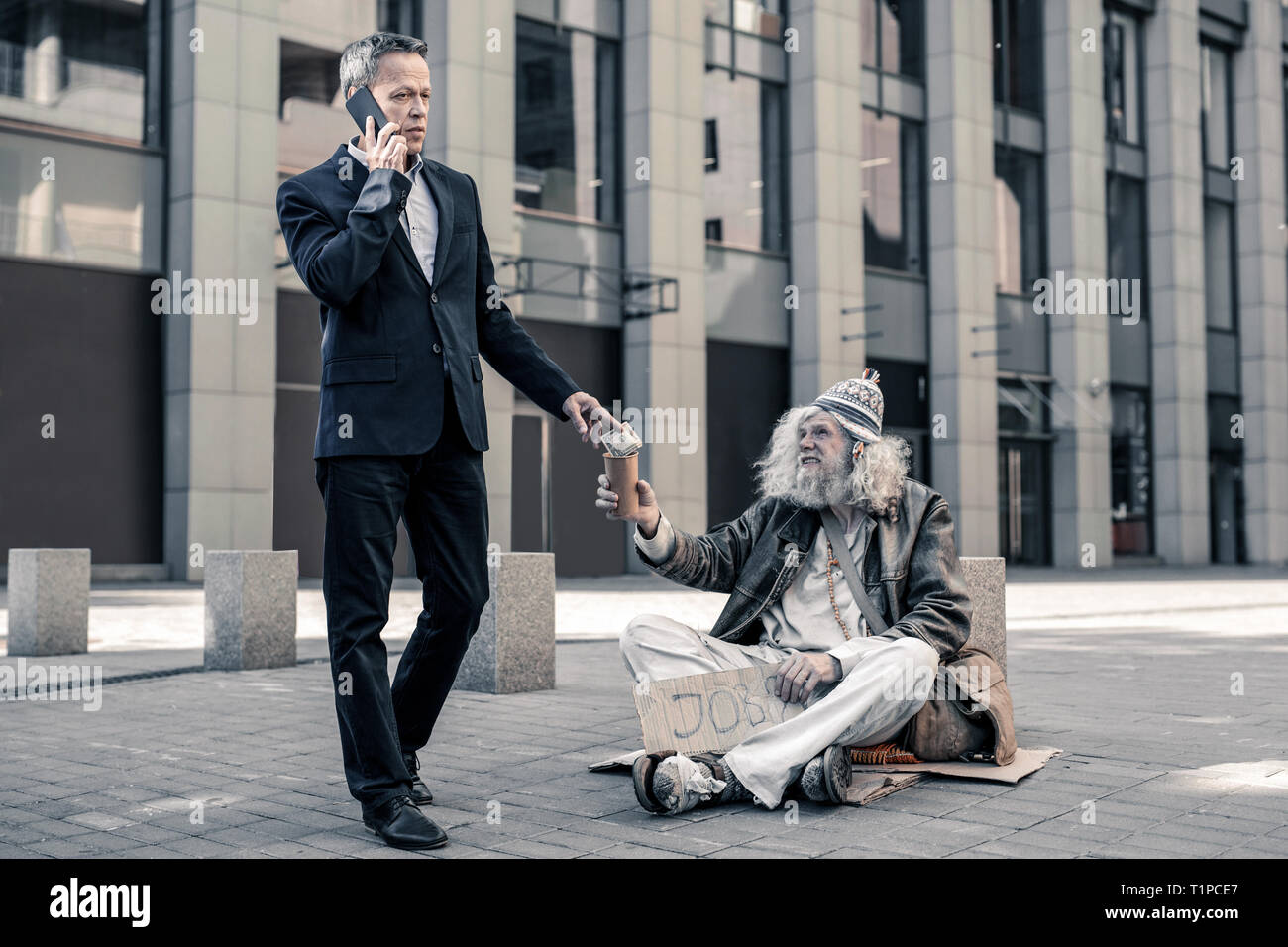 Thankful grey-haired senior homeless looking on business man - Stock Image