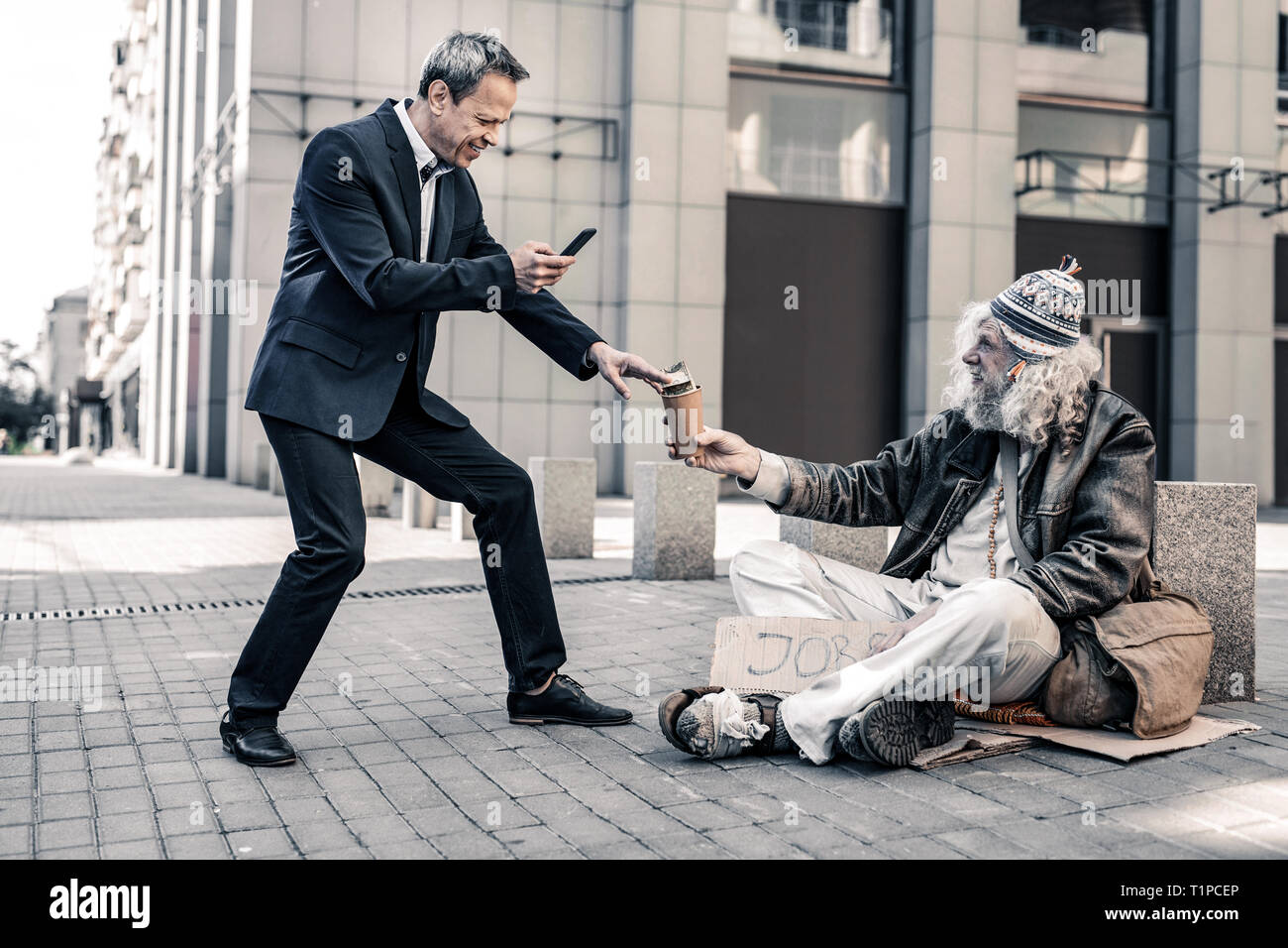 Vain rich man making selfie of himself with dirty homeless - Stock Image