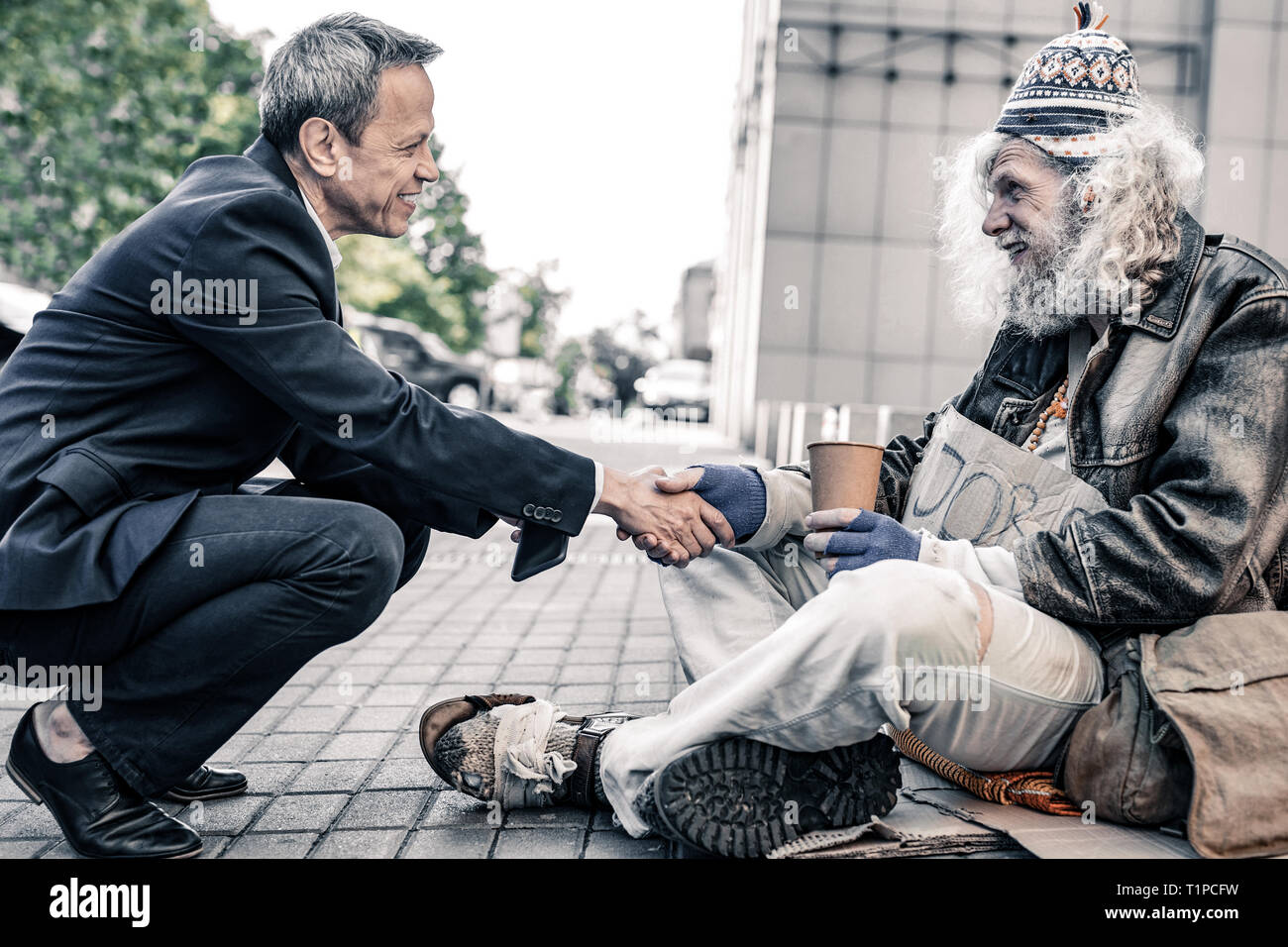 Curious short-haired businessman sitting in front of long-haired homeless - Stock Image