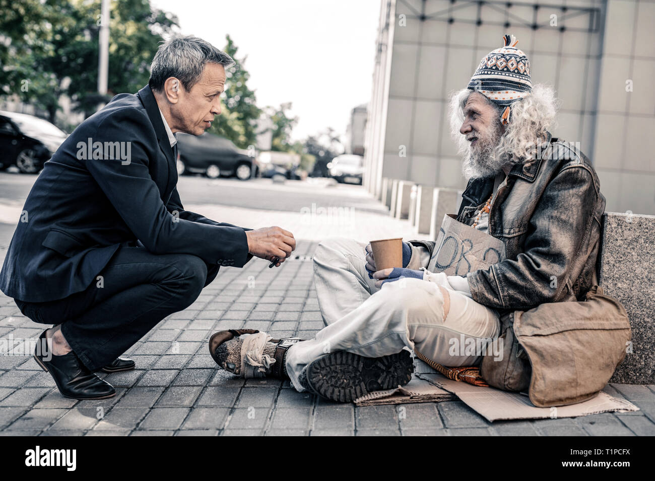 Pleasant short-haired rich man in costume supporting miserable homeless - Stock Image