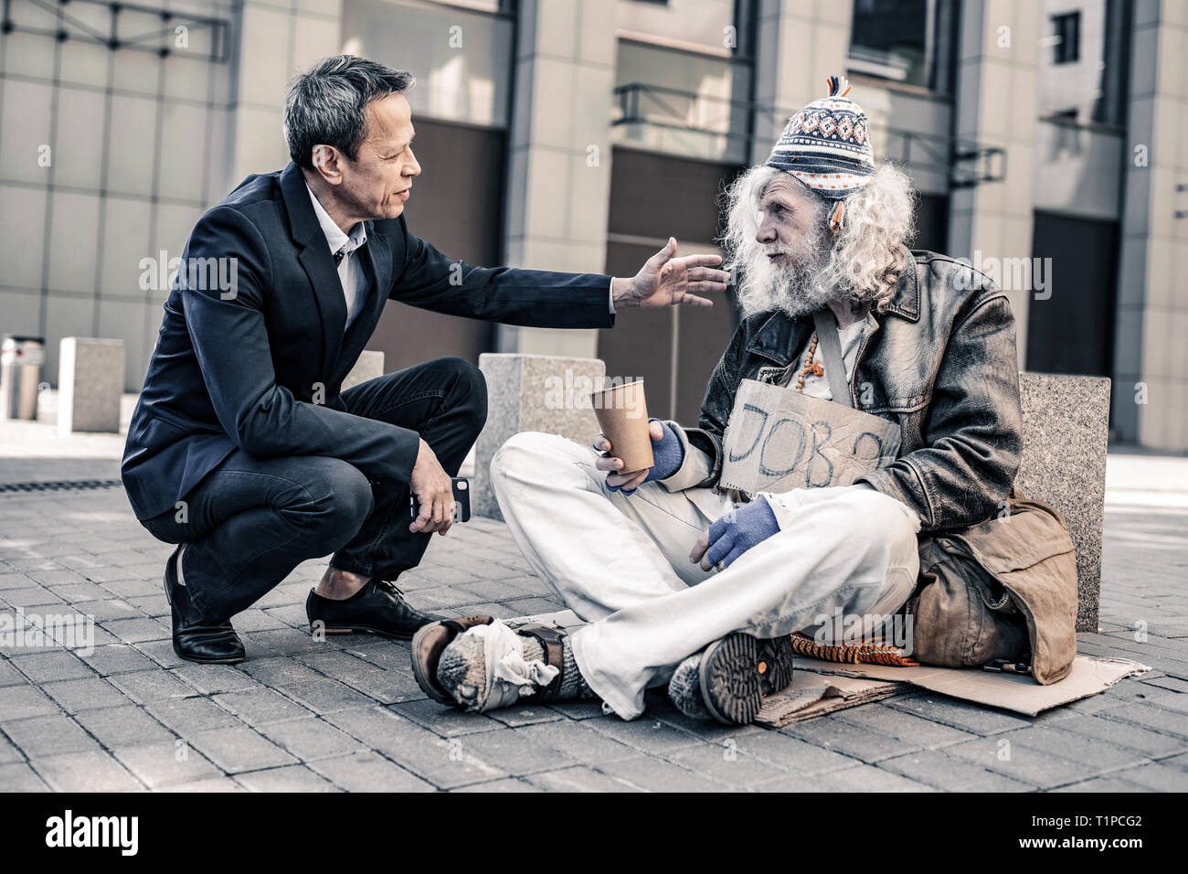 Helpful caring man in costume putting hand on shoulder of dirty homeless - Stock Image