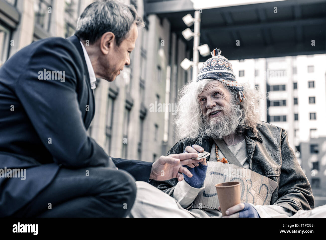 Dirty miserable homeless man taking dollar bill from hands of kind man - Stock Image