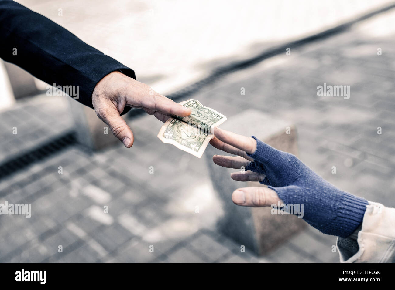 Caring man putting money in hands of needed old man - Stock Image