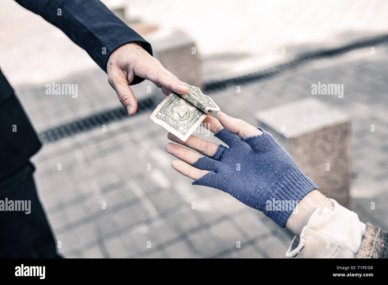 Pedestrian in dark costume carrying money bill and gifting it - Stock Image