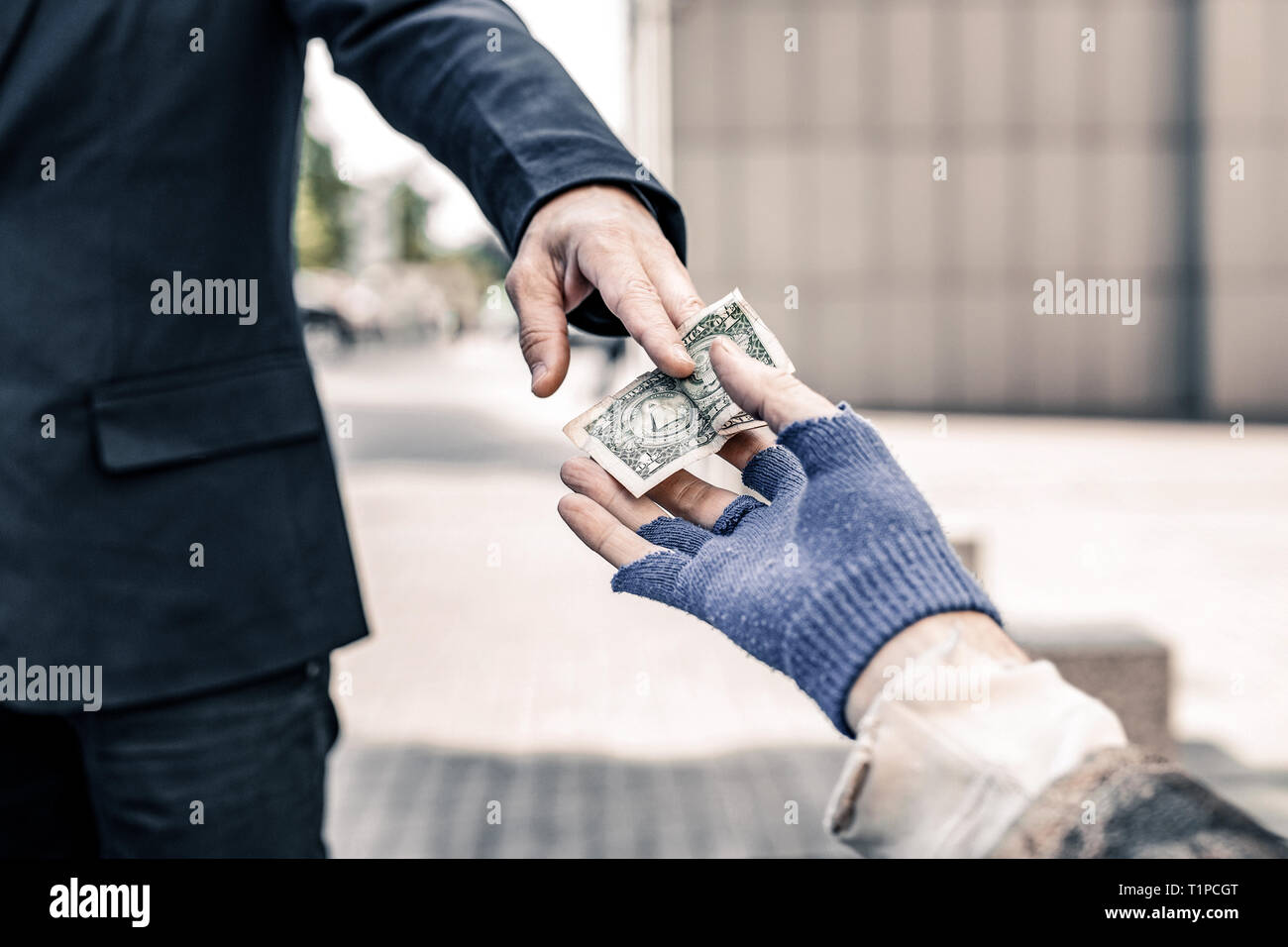 Beneficent man in dark business costume holding out money - Stock Image