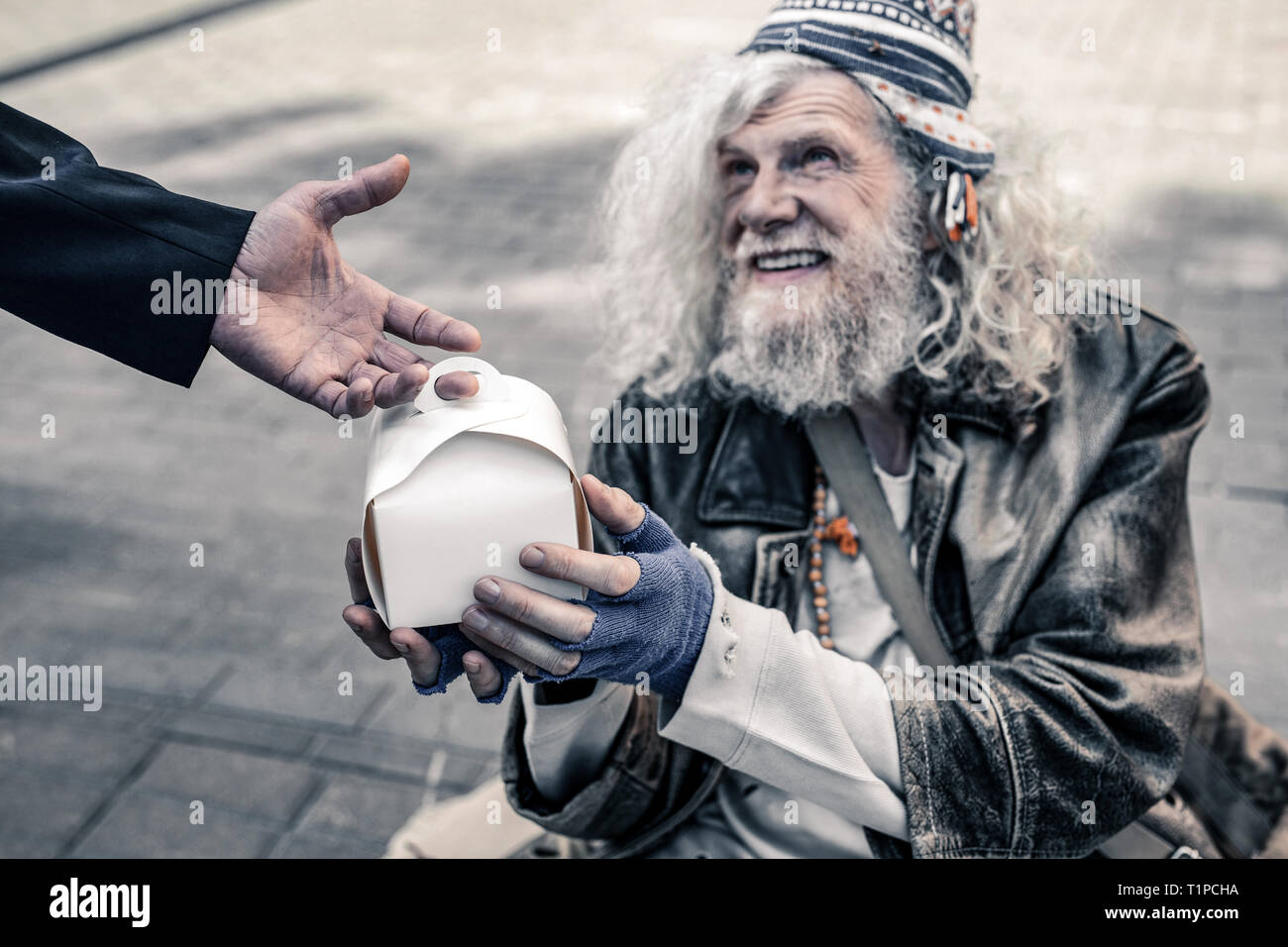 Cheerful long-haired old man living on the street and holding box with food - Stock Image