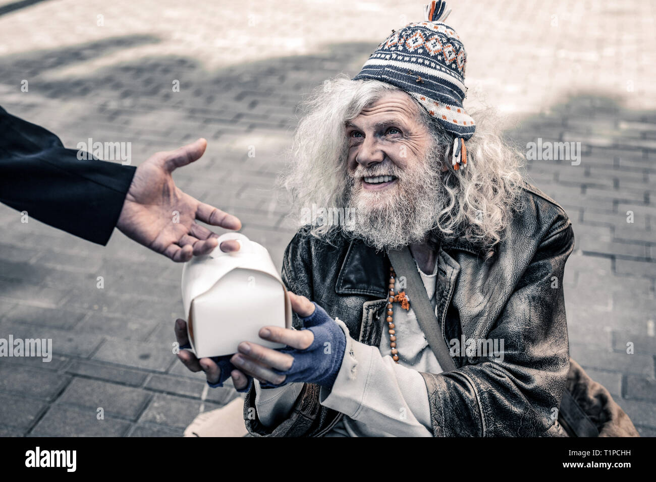 Dirty grey-haired senior homeless wearing ragged clothes and receiving food - Stock Image