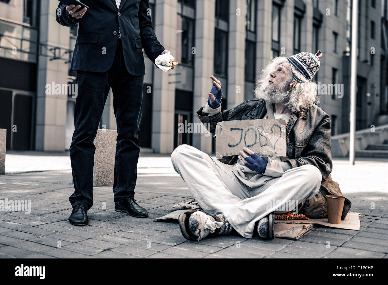 Grey-haired senior homeless carrying nameplate and taking bite food - Stock Image