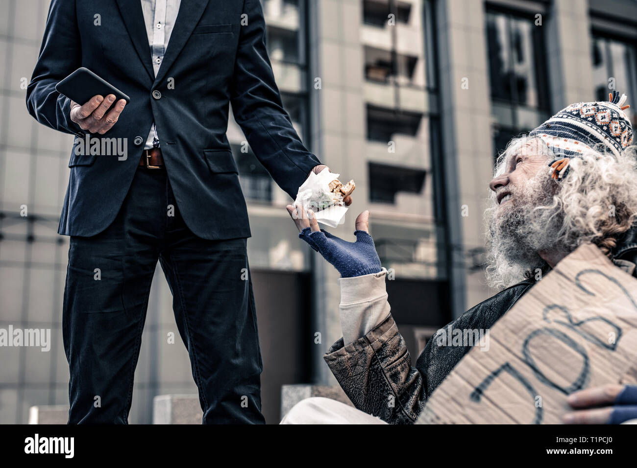 Desperate starving old man sitting on cold ground and begging for food - Stock Image