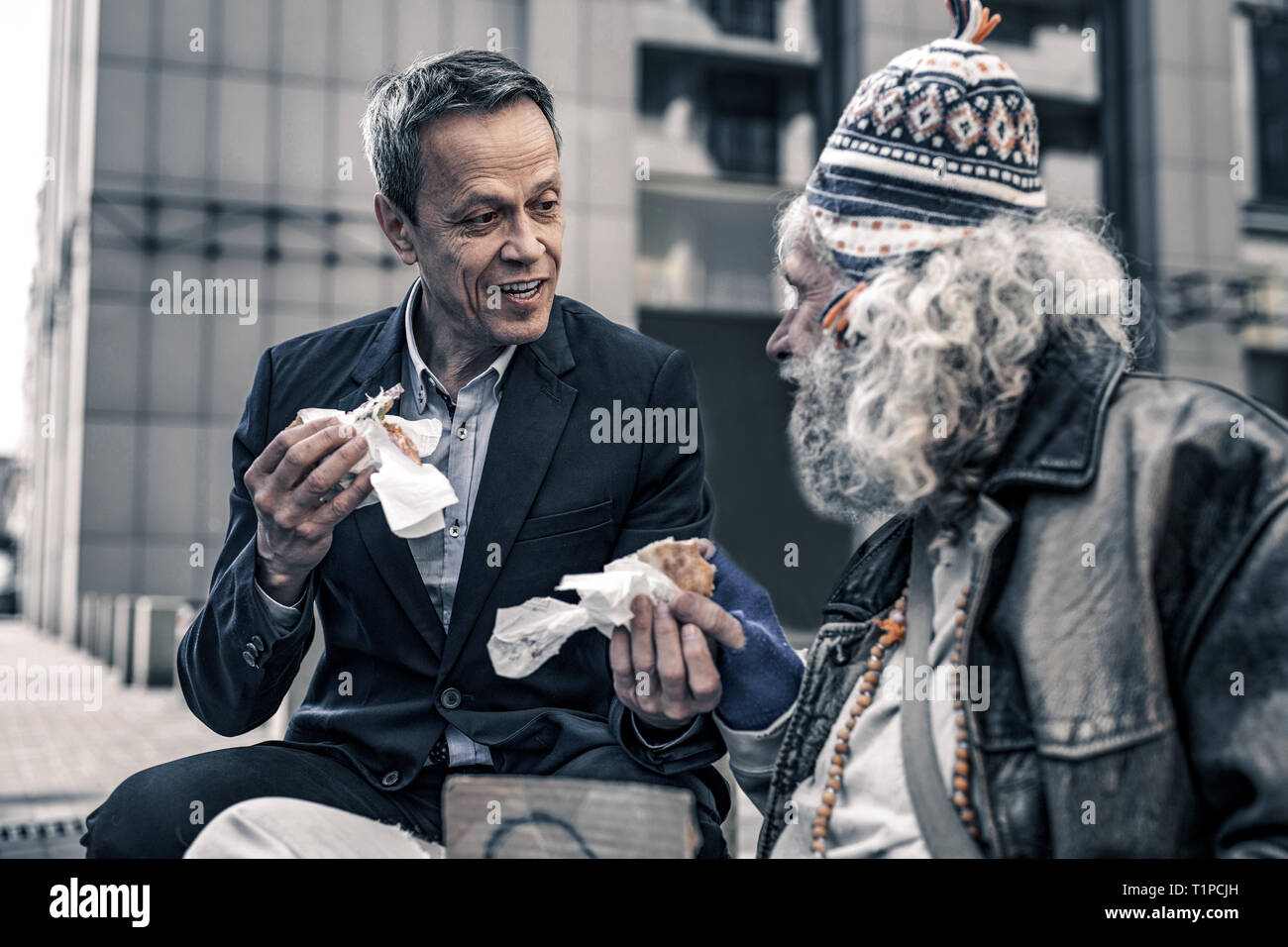 Communicative kind man talking to grey-haired senior homeless - Stock Image