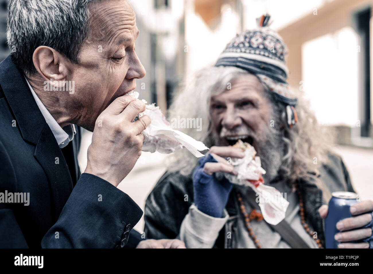 Caring short-haired business man and poor old man biting pieces of sandwich - Stock Image
