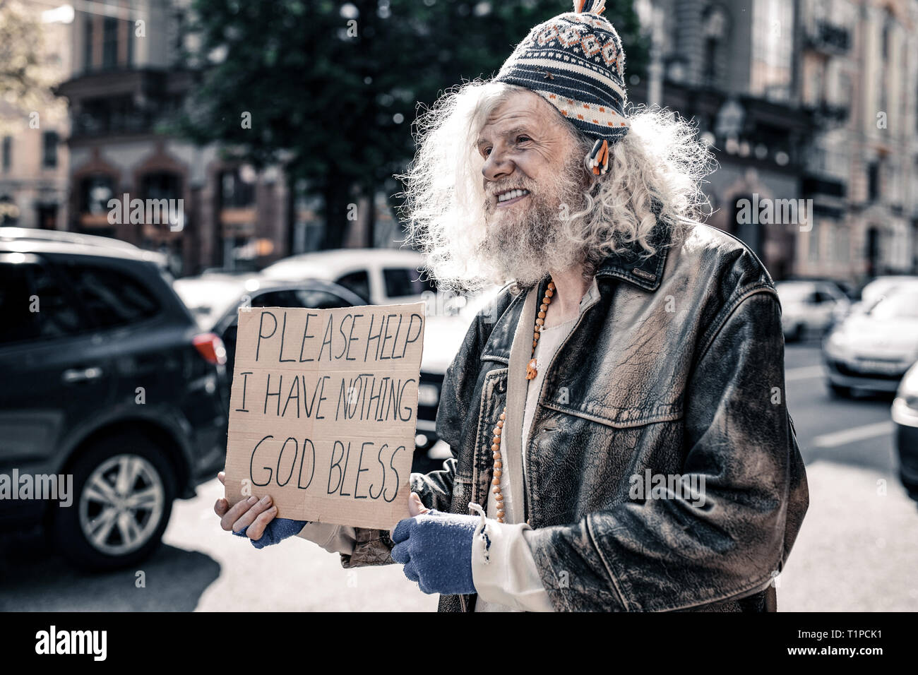 Long-haired desperate senior homeless wearing ragged clothes - Stock Image