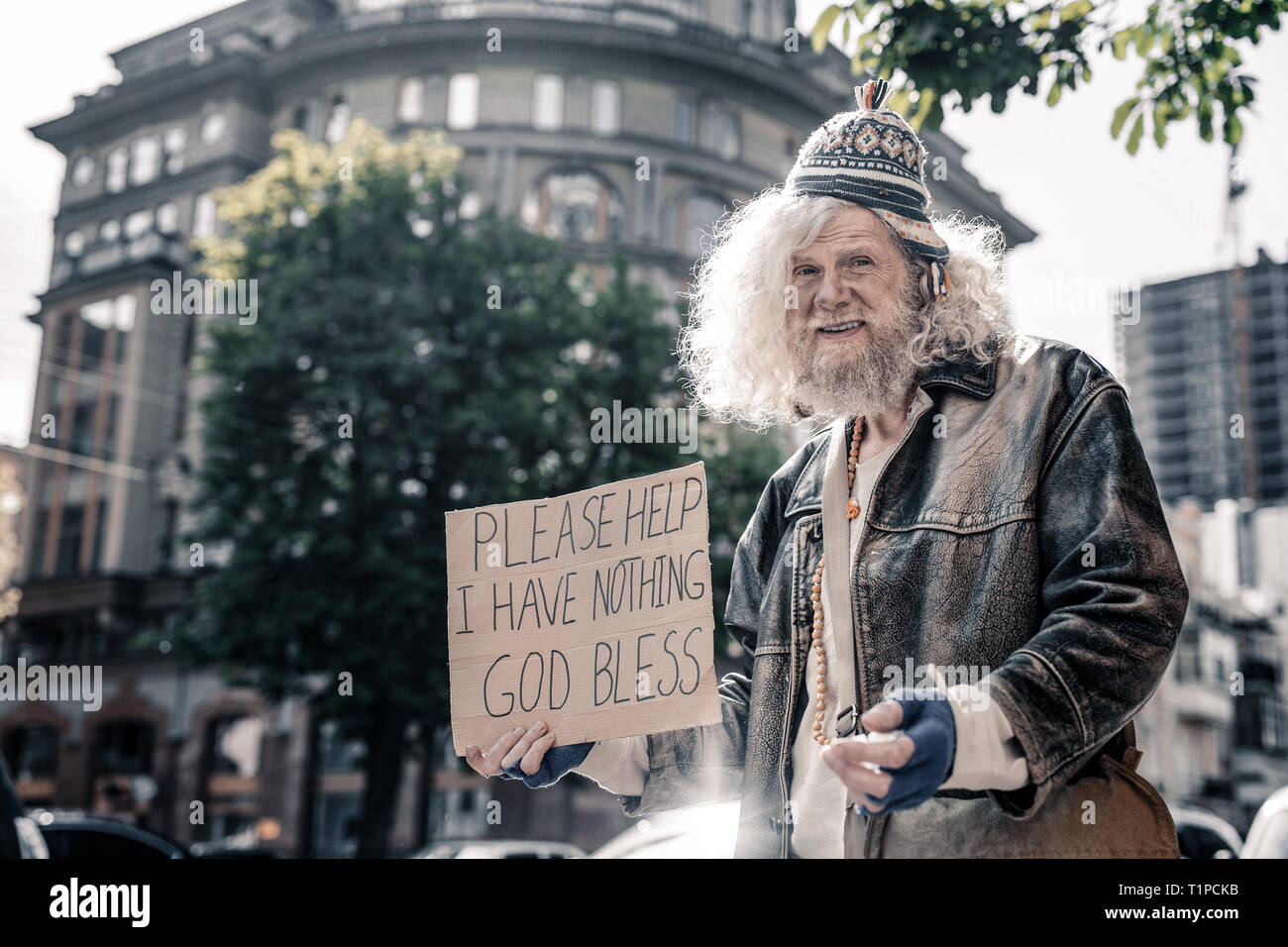 Confused senior homeless man being dirty and washed - Stock Image