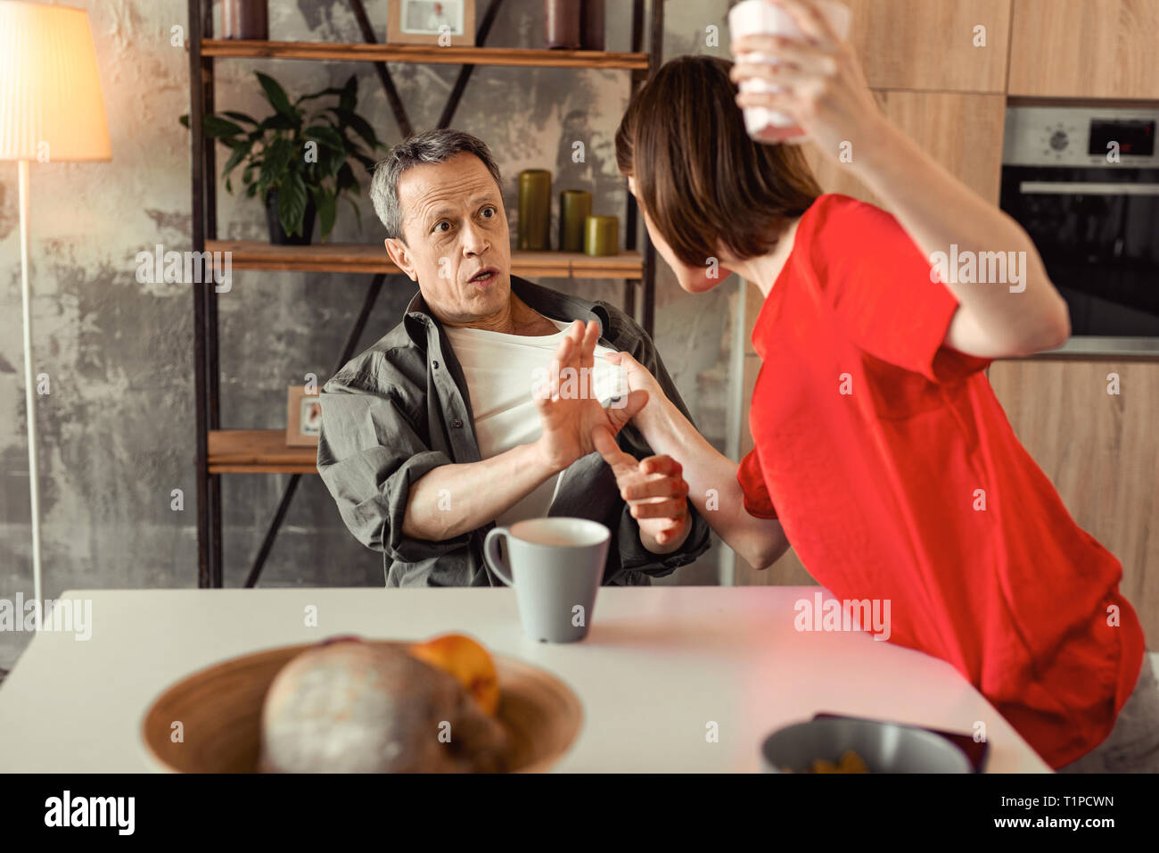 Scared and shocked man stopping his crazy wife - Stock Image
