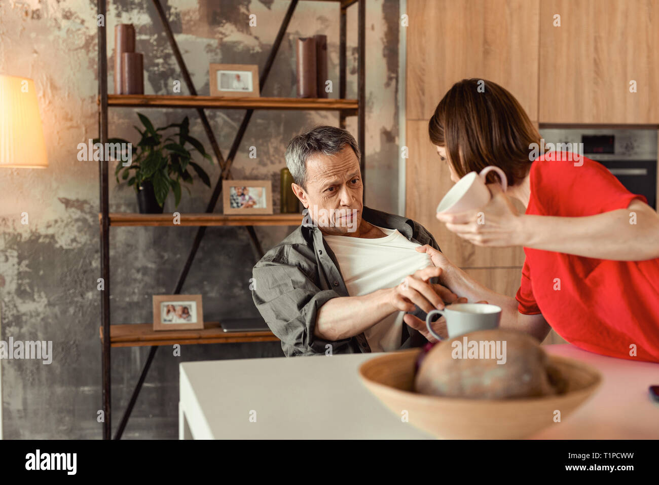 Serious adult man asking his mad wife calm and serenity - Stock Image