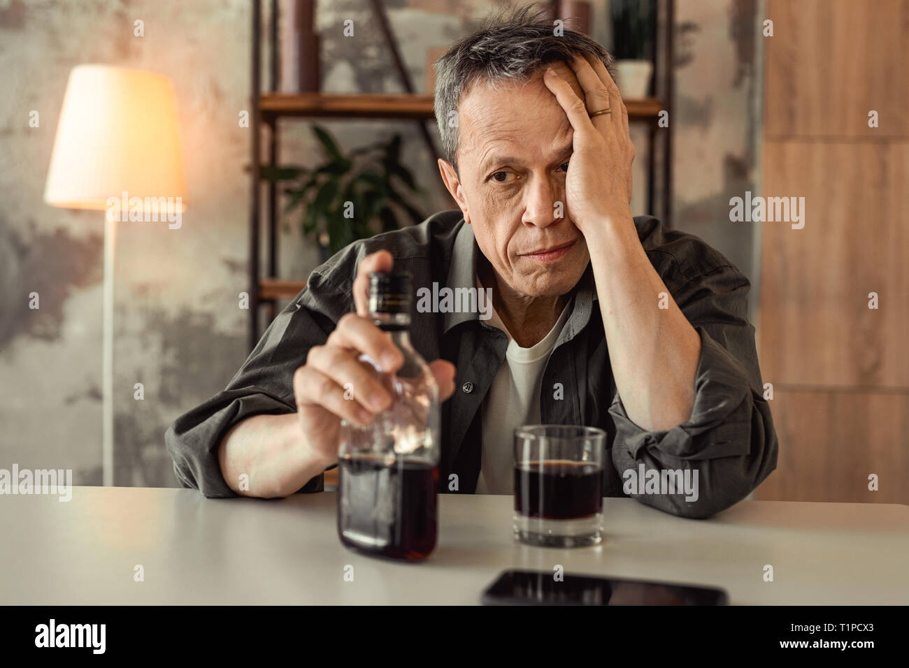 Desperate old alcoholic sitting in front of glass bottle with rom - Stock Image
