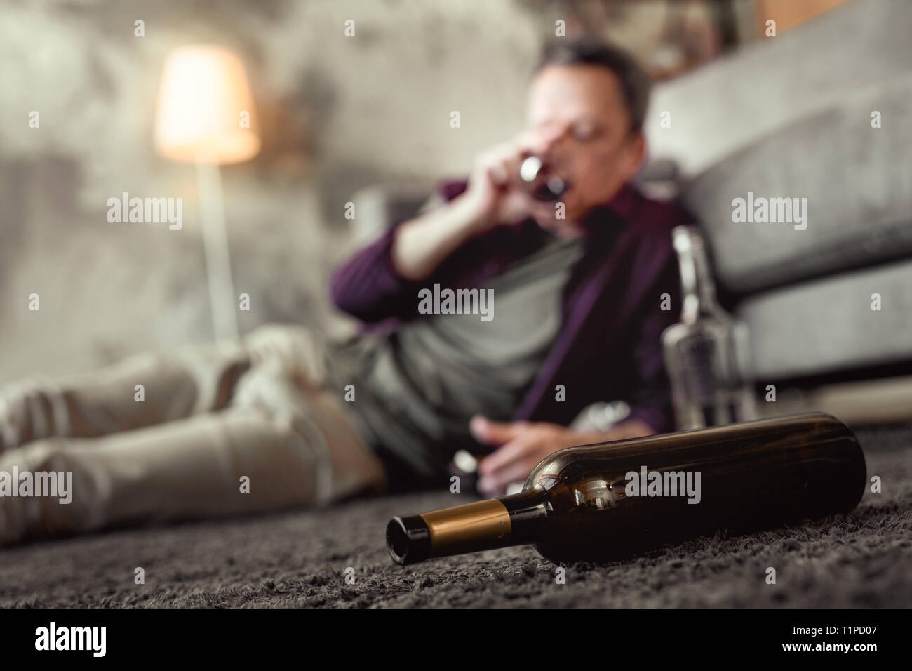 Adult man lying on carpet in living room with empty bottles around - Stock Image