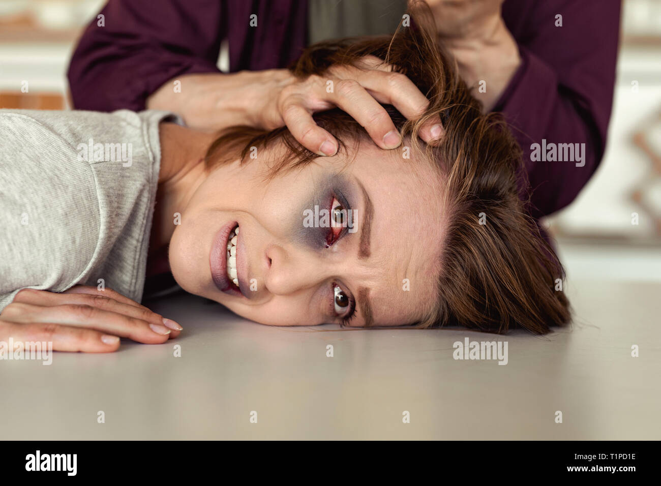 Desperate woman with bruised eye praying for life - Stock Image