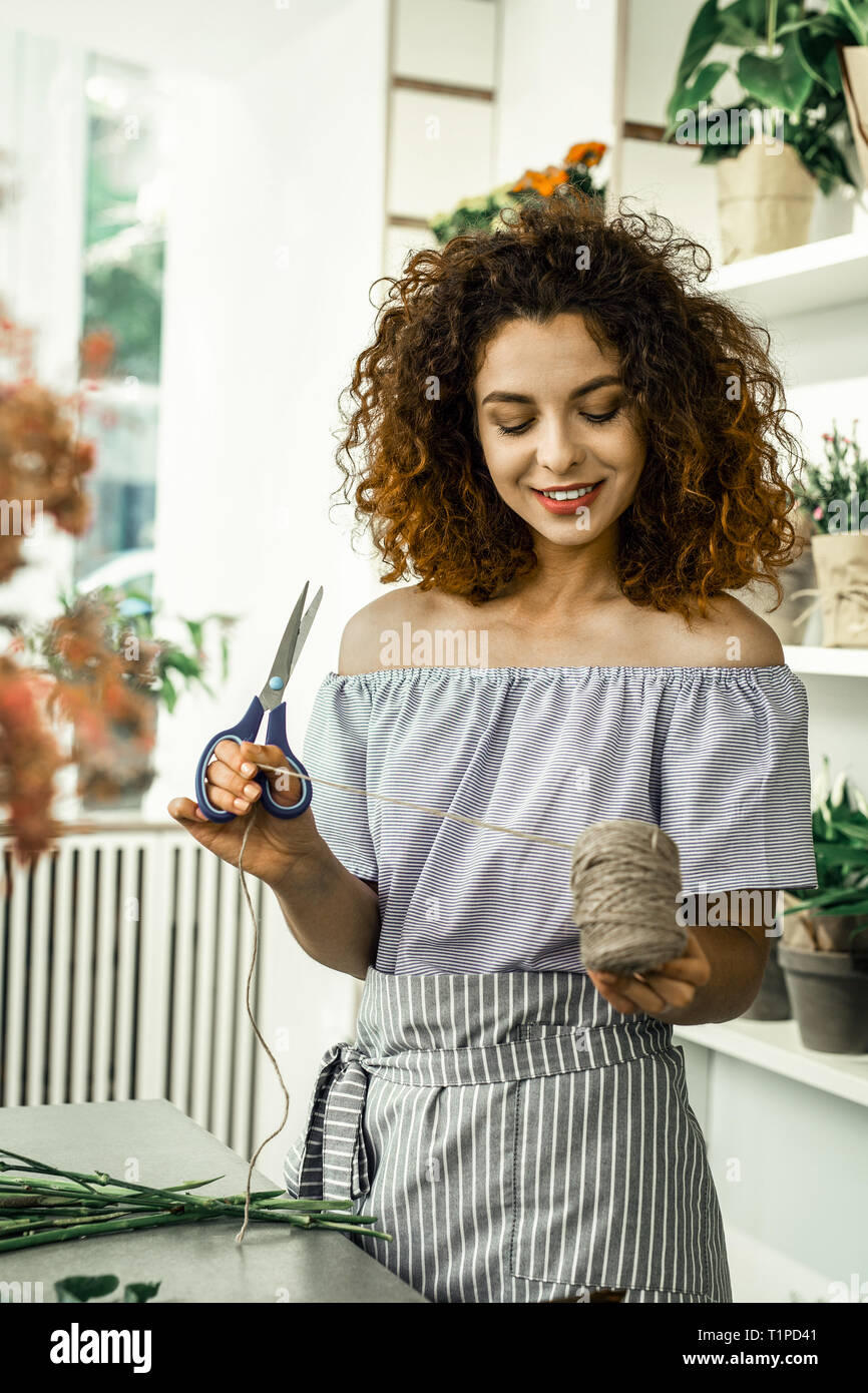 Red-haired curly woman working in flower shop feeling joyful and excited - Stock Image