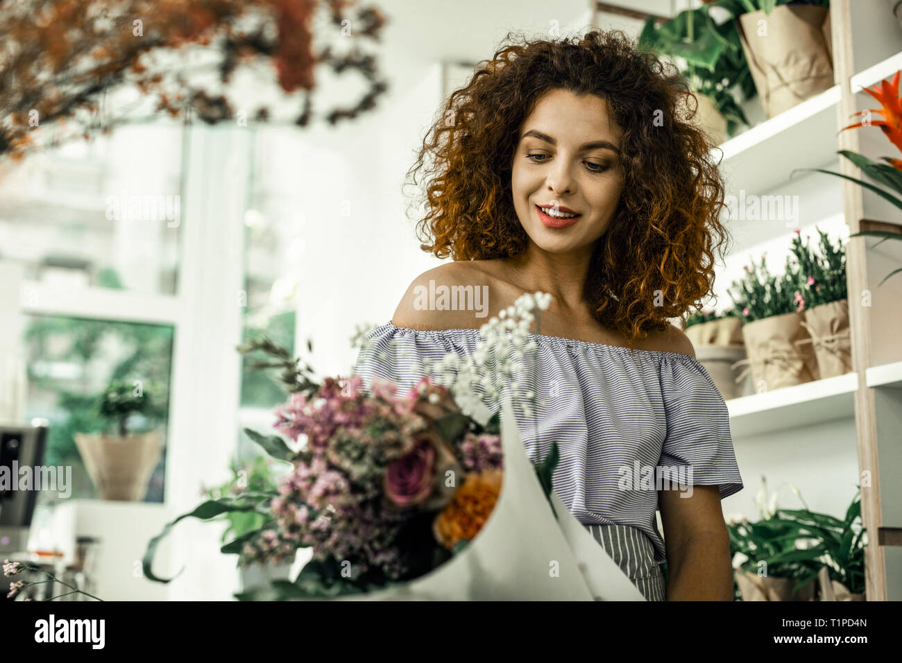 Curly florist feeling satisfied while looking at nice perfect bouquet - Stock Image