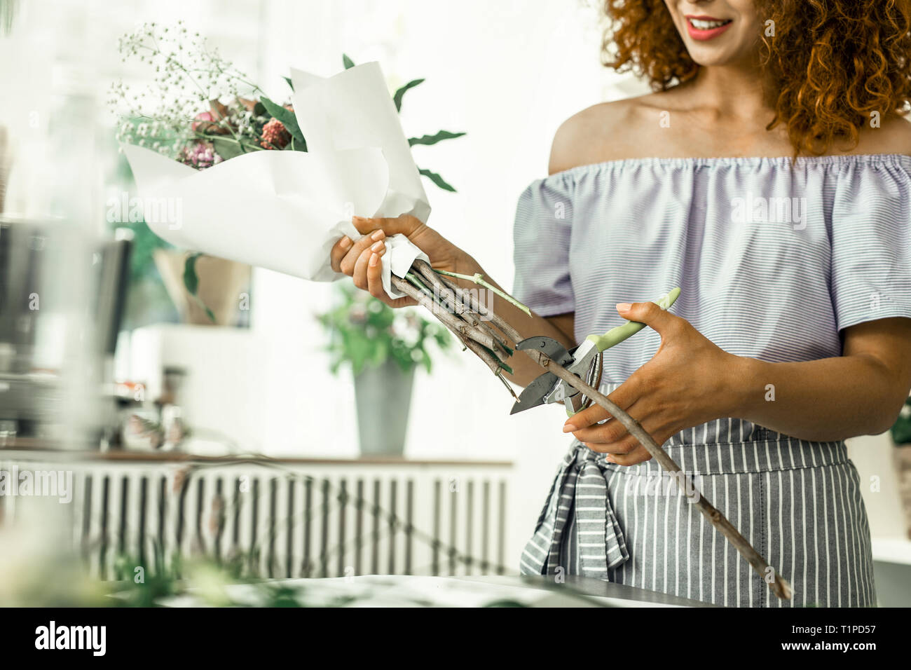 Curly red-haired florist with bright lips finishing beautiful nice bouquet - Stock Image