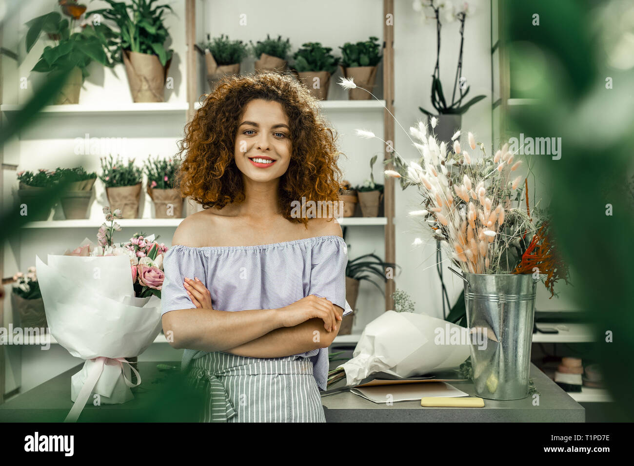 Young appealing student enjoying her part-time job in big floral shop - Stock Image