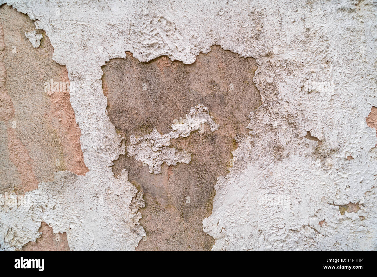 Cracked painted rendering exposing concrete or cement structure beneath. Seen better days metaphor. Old paint texture. - Stock Image