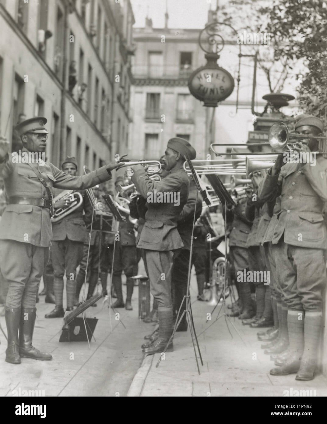 Genuine jazz for the yankee wounded In the courtyard of a Paris hospital for the American wounded, an American negro military band, led by Lt. James R. Europe, entertains the patients with real American jazz. Photograph shows African American musicians in the 369th Infantry Regiment band led by James Reese Europe. 1918 - Stock Image