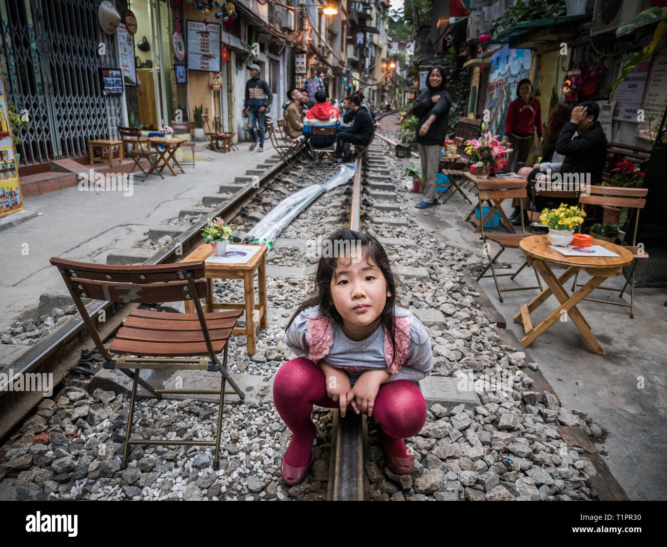 Curious Vietnamese girl squatting on rails and looks into camera in train street of Hanoi City, Vietnam - Stock Image