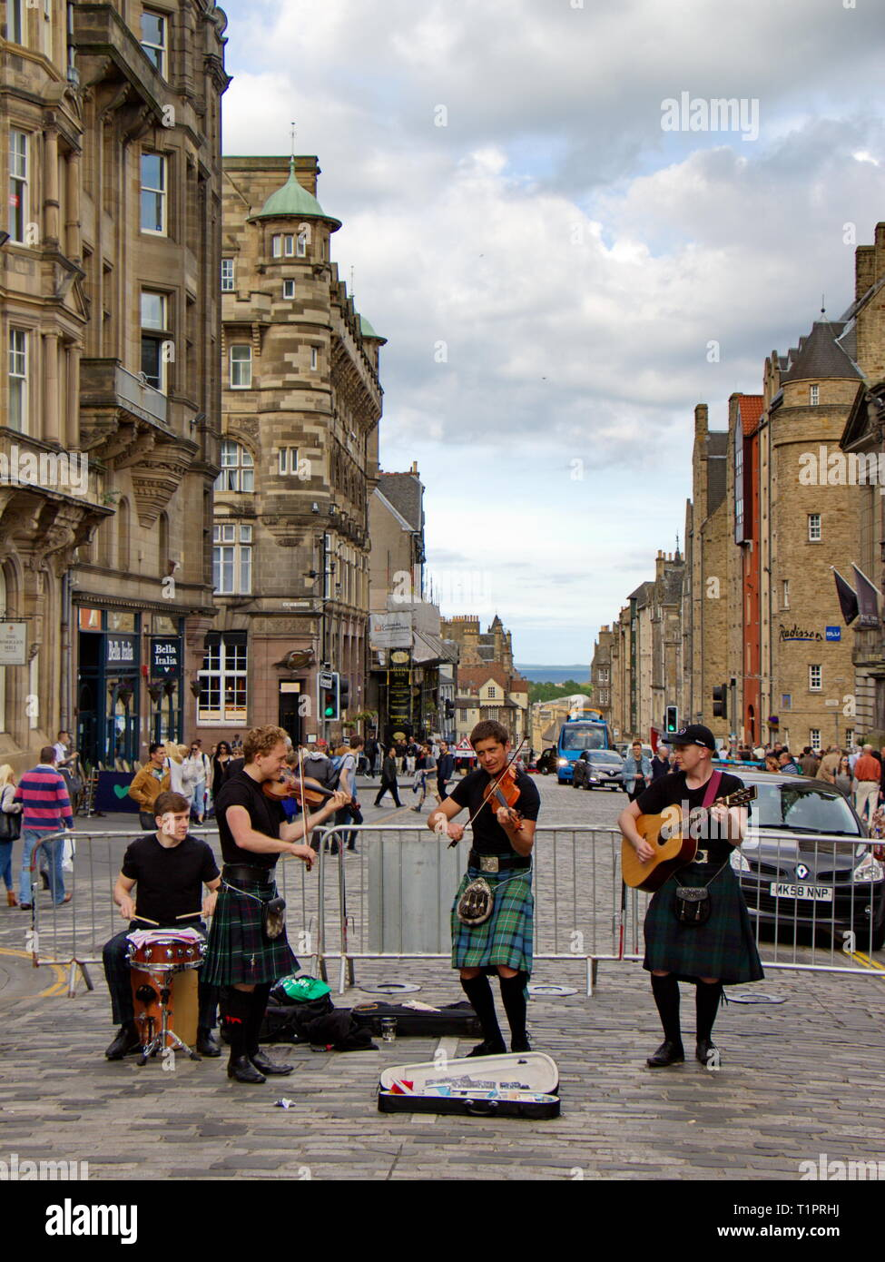 music band dressed in traditional skirts and playing on bagpipes on Royal mile street - Stock Image