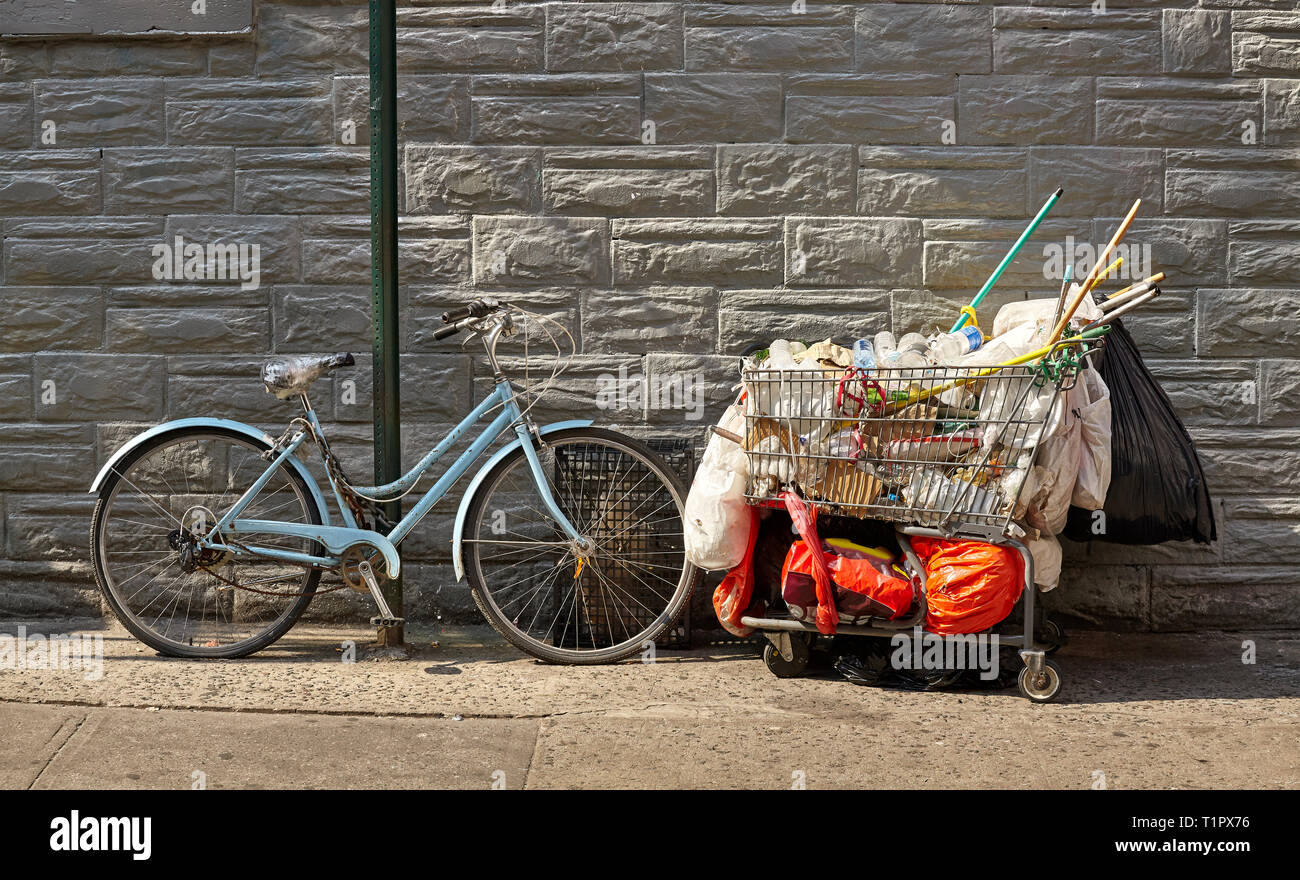 Old bike and shopping cart filled with garbage on a street of New York City, USA. - Stock Image