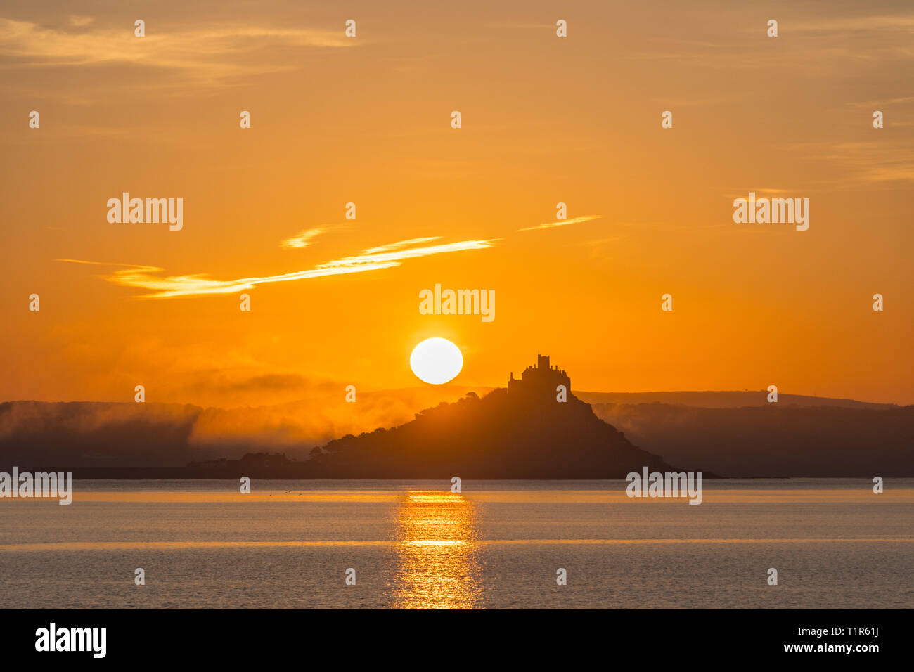 Penzance, Cornwall, UK. 28th Mar, 2019. UK Weather. The sun rises above St Michaels Mount, with mist rolling in from the land this morning. Credit: Simon Maycock/Alamy Live News Stock Photo