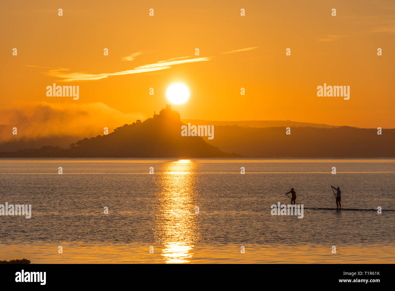 Penzance, Cornwall, UK. 28th Mar, 2019. UK Weather. Paddleboarders were out at 5am this morning to make it across the sea at Mounts bay the for the sunrise over St Michaels Mount. Credit: Simon Maycock/Alamy Live News Stock Photo