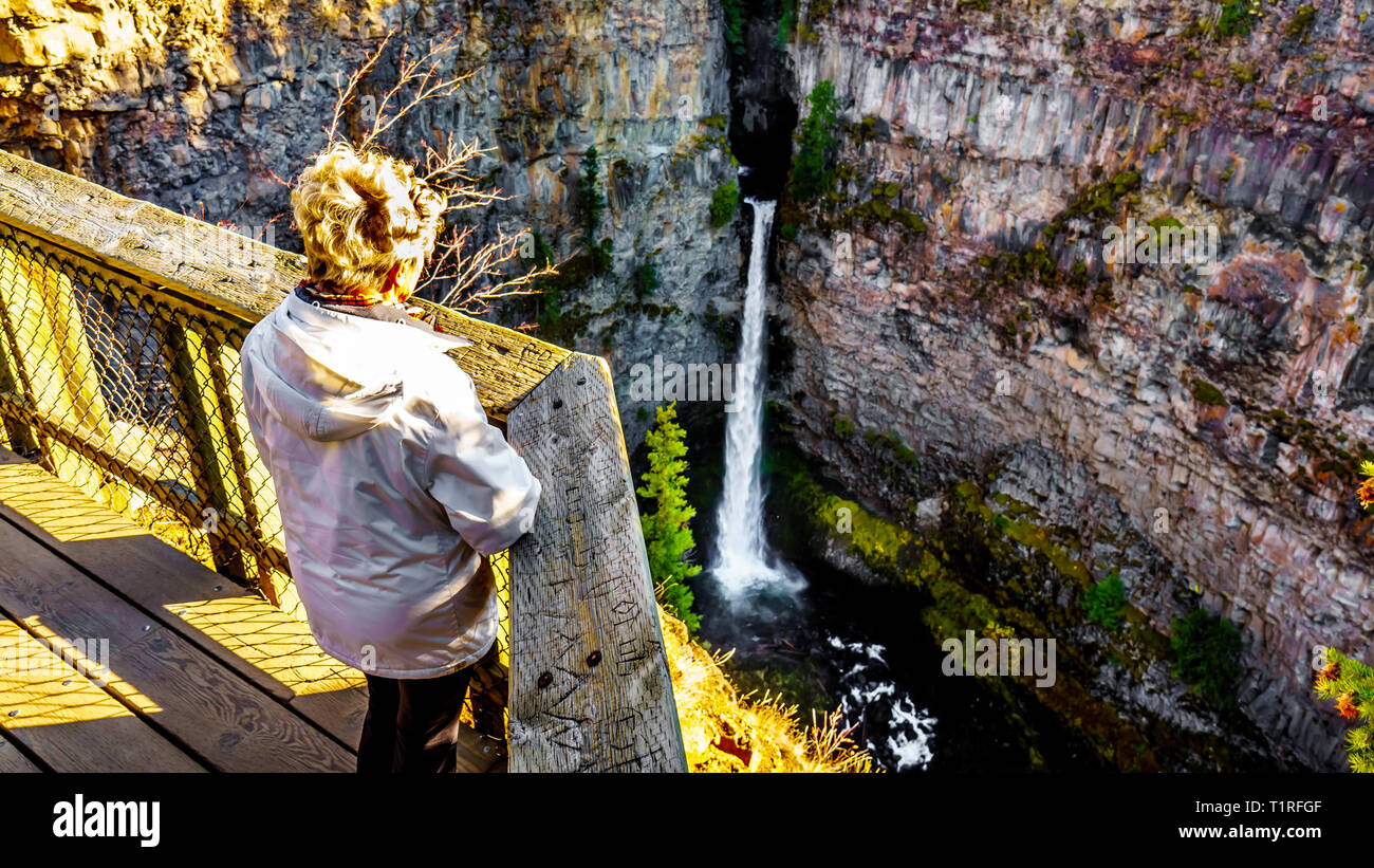 Senior woman looking at Spahats Falls on Spahats Creek from the viewing platform in Wells Gray Provincial Park at Clearwater British Columbia, Canada Stock Photo