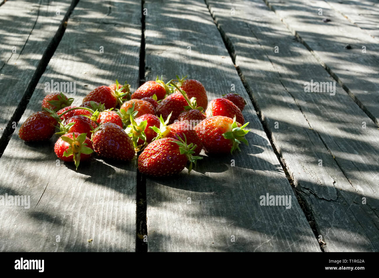 Strawberry on rustic wooden table close up - Stock Image