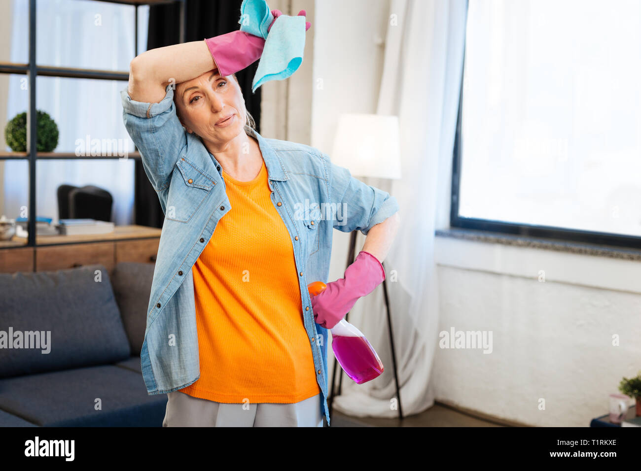 Tired woman in bright t-shirt wiping sweat from her forehead - Stock Image