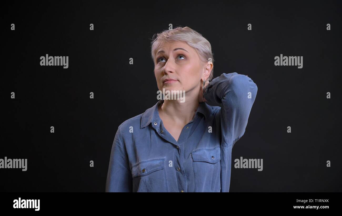 Closeup portrait of adult attractive caucasian female with short blonde hair being confused and rubbing her neck with background isolated on black - Stock Image